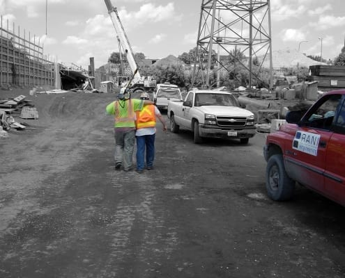 Two surveyors walking on construction iste